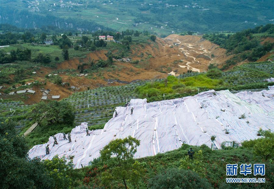 7月23日,抢险人员在恩施屯堡乡马者村山体滑坡现场进行铺设油布作业(无人机照片)。新华社记者 肖艺九 摄