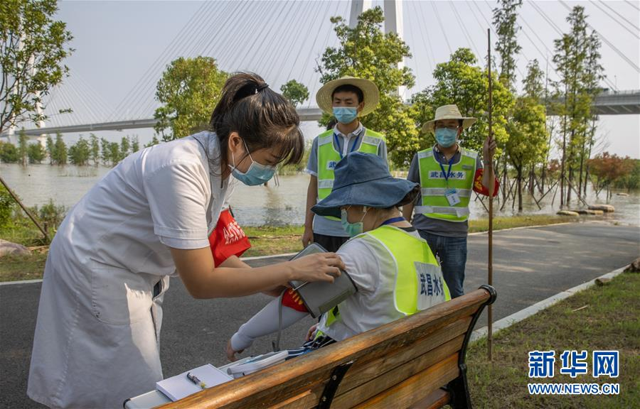 7月24日,在武汉青山江滩罗家港防汛值守哨棚旁,武昌区杨园街社区卫生服务中心医务人员为巡堤员测量血压和心率。从7月6日开始,该中心医务人员携带医药箱和消毒器具每天两次往返于3.7公里的长江岸堤,为巡堤员测量血压、监测体温,并宣传防疫知识。新华社记者 肖艺九 摄