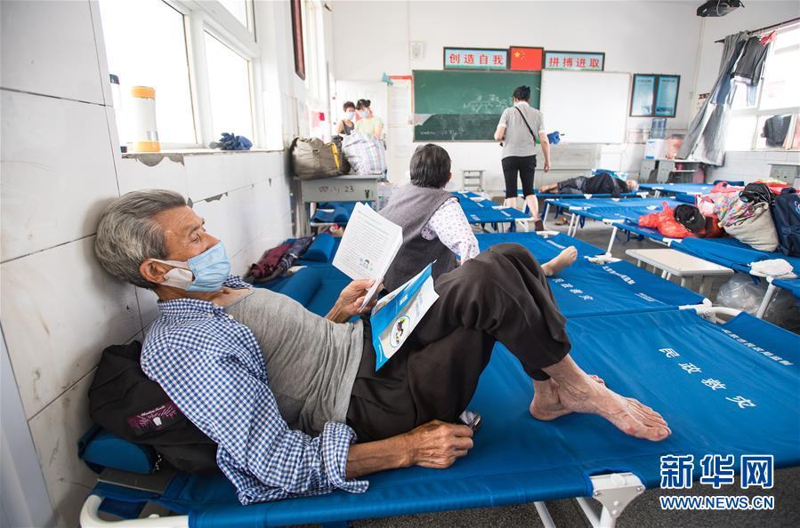 7月9日,村民戴口罩在湖北省黄梅县濯港镇十里益海小学集中安置点休息。新华社记者 肖艺九 摄