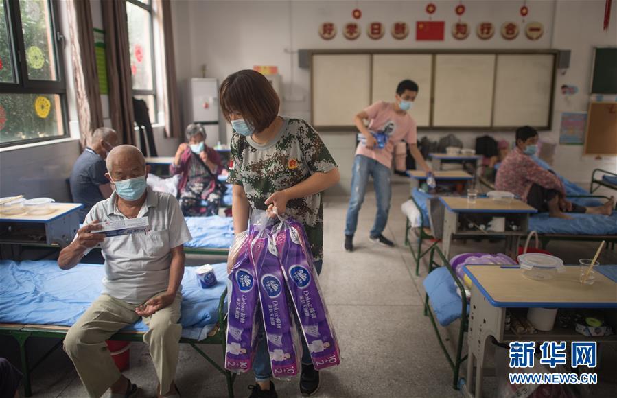 7月7日,在武汉街道口小学东方雅园分校安置点,工作人员为天兴乡村民发放生活物资。新华社记者 肖艺九 摄